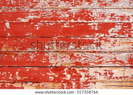 Texture of ancient wood with cracked paint of red color