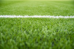 Texture of artificial grass herb cover sports field. It is used in different sports: football, tennis, baseball, soccer, american football, cricket, golf, field hockey, rugby.