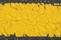 Texture of asphalt road with yellow line background, pattern of old cracked yellow painted on asphalt surface can use for background and wallpaper, close up