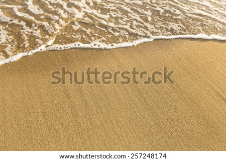 Texture of beach sea sand with a soft wave of surf.