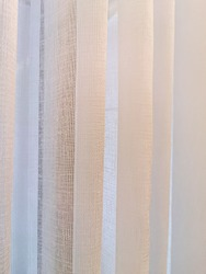 Texture of beige curtain for background with sun light in morning, Close up surface of sheer curtain, Selective focus.