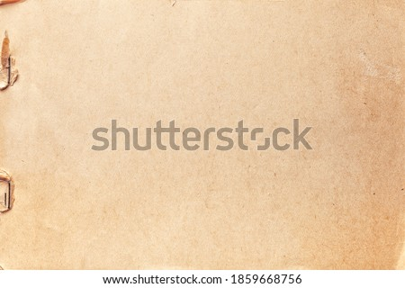Texture of beige old paper with rust clip, crumpled background. Vintage brown grunge surface backdrop. Craft notebook with staple. Stockfoto ©