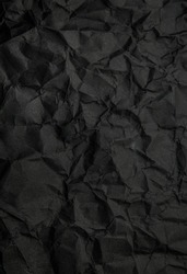 Texture of black crumpled paper. Dark paper background with chaotic bends. A sheet of black wrinkled paper