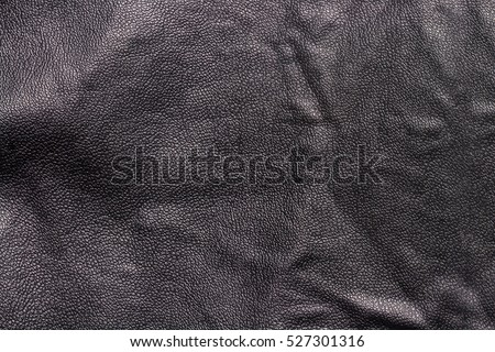 Texture of black leather on the back of a black leather jacket