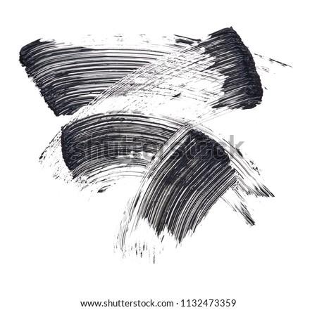 Texture of black mascara for eyelashes isolated on white background. Smear of black mascara for eyelashes on white background. Black mascara smears on white background