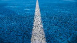 Texture of blue rubber running track with white stripe in the middle. Selective focus, blur. Running track at the stadium close up