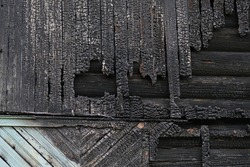 Texture of burnt wooden house. Background of black burned boards on destroyed by fire building.