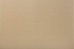 Texture of corrugated light beige paper, macro. Striped pattern of brown cardboard background, closeup.