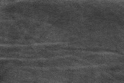 texture of dark worn black denim close-up for empty background or for desktop wallpaper