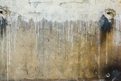 Texture of dirty destroyed yellow wall with white paint leaks