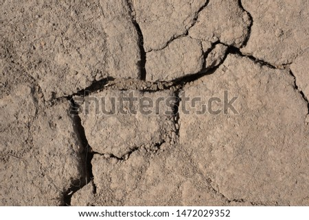 Texture of dry cracked earth. Deep cracks in the brown land soil, hot climate and drought.  #1472029352
