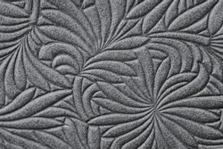 Texture of genuine leather embossed floral pattern close-up, trendy grey color. Modern natural background