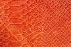 Texture of genuine rough leather close-up, imitation of the skin of scaly exotic reptile, fashion bright orange red color, modern background