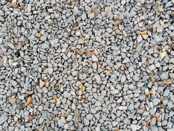 Texture of gravel with dry autumn leaves