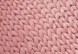 Texture of pink big knit blanket. Large knitting. Plaid merino wool. Top view