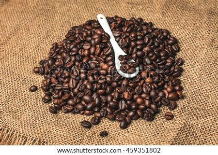 Texture of roasted coffee ready to drink with a white top teaspoon. #459351802