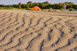 Texture of sand dunes in the soft light of the setting sun on the background of a tourist camp with boats and a campfire site
