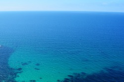 Texture of sea shore with clear turquoise water and sandy bottom. Sea classic blue surface aerial top view. Summer beautiful blurred Background. Selective soft focus.