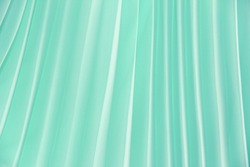 texture of synthetic green fabric with decorative pleats