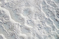 Texture of travertine. Ribbed surface formed by flowing mineral water from geothermal hot spring
