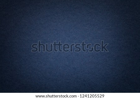 Texture of vintage dark denim paper background with vignette. Structure of dense navy blue kraft cardboard with frame. Felt gradient backdrop closeup.