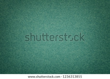 Texture of vintage dark green paper background with vignette. Structure of dense emerald kraft cardboard with frame. Felt gradient backdrop closeup.