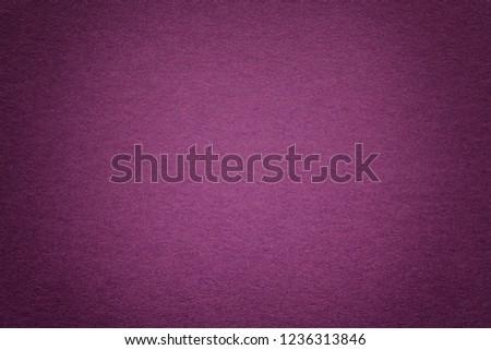 Texture of vintage dark purple paper background with vignette. Structure of dense magenta kraft cardboard with frame. Felt gradient backdrop closeup.