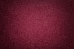 Texture of vintage dark red paper background with vignette. Structure of dense maroon kraft cardboard with frame. Felt wine gradient backdrop closeup.