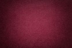 Texture of vintage dark red paper background with vignette. Structure of dense maroon kraft cardboard with frame. Felt wine gradient backdrop closeup.