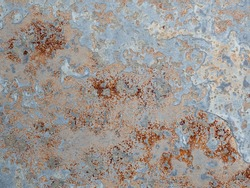 Texture of wall with brass and aqua patina. Blue silver surface with streaks of rust. Rusty corrosion. Brown, grey, blue and orange rust on enamel. Corroded background.