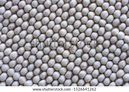 Texture of warm woolen white rug / bee honeycomb pattern, soft focus.