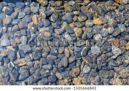 Texture of wet pebbles. Smooth pebbles under clear water. Striped stones at the bottom underwater create a fresh texture.