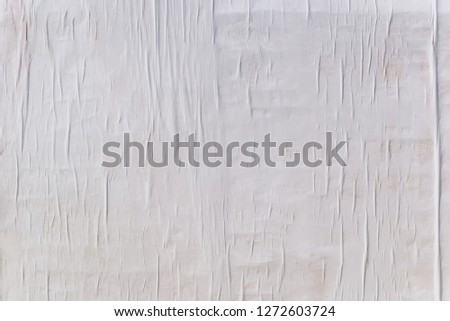 Texture of wet white folded paper on an outdoor poster wall, crumpled paper background. #1272603724