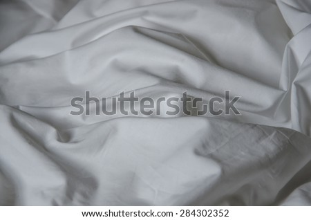 Texture of white fabric wrinkled. Bed sheet crumpled. Messy bed
