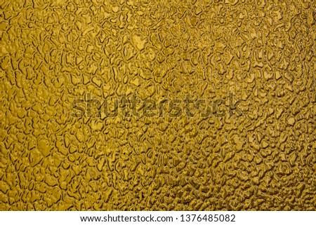 Texture of yellow frosted glass. Background with free space for text or design. Rough glistening rough surface