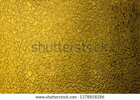 Texture of yellow frosted glass. Background with free space for text or design. Rough glistening surface