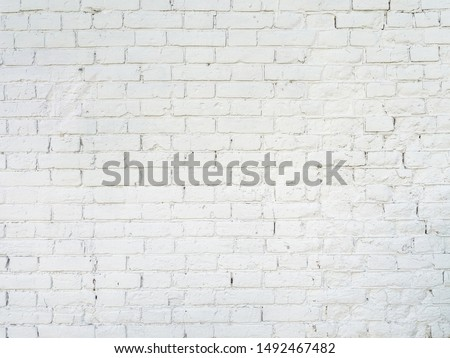 texture: old cracked brick wall painted in white paint