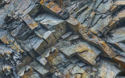 Texture or background layers and cracks in sedimentary rock on cliff fake, selective focus. Cliff of rock mountain, soft focus. Rock slate in the mountain. Cracks of sandstone.
