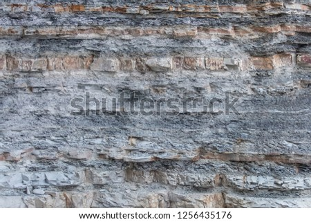 Texture Or Background Of Cut Of Breakaway Rock. Layers Of Rock Cut. Grey Layered Background #1256435176