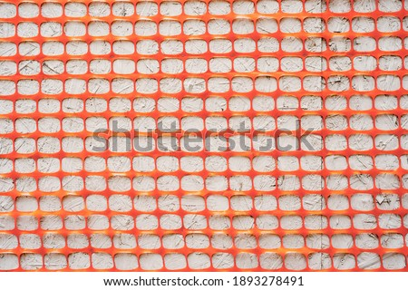 Texture Orange fence construction mesh close-up on a gray background. Foto d'archivio ©