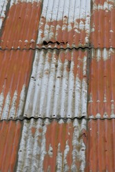 Texture, patterns and bolts on rusty old corrugated iron roof