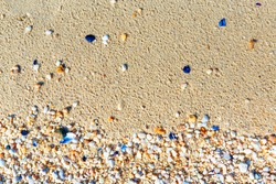 Texture with shell and pebble at wet yellow sand of beach. Vacation background.