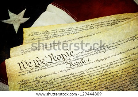 Textured American Constitution lying over top of the US flag.