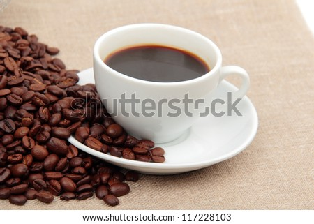 Textured background of dark brown roasted coffee beans background and cup of coffee on Food and Drink conceptual theme