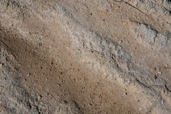 Textured background seen from above looking sandy, gravel stones and mud with sunlight