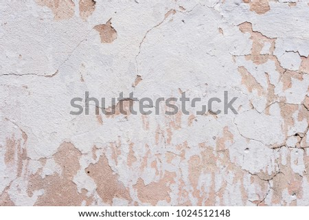 Textured background white cracked plaster partially sprinkled with a pink shaded cracked wall. Grunge background