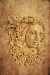 Textured Background with bust head of a Greek maiden with grapes leaves in statue form/Textured Background of Grape haired Greek woman sconce statue
