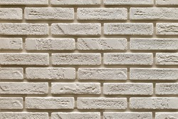 Textured beige brick wall, stone texture. decorative tiles for wall decoration. Background,  beige decorative brick. loft decor style. structural surface, imitates old brick