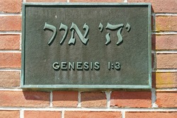 textured bronze plaque hanging on a red brick wall with the Hebrew text for