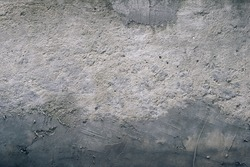 Textured concrete wall with gradient from light to dark grey, scuffed and smudged with cement. Grunge texture and background concept.